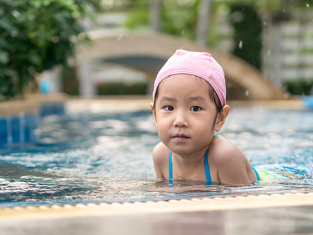 Asian kid is playing in the pool
