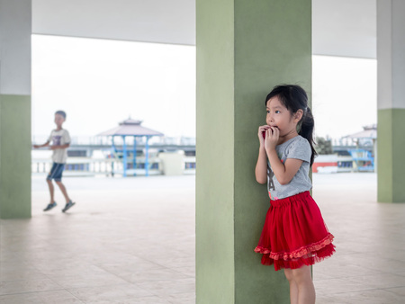 cute girl playing hide and seek with her brother Stock Photo