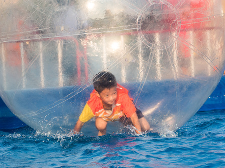 floating on water: Young Asian boy playing inside a floating water walking ball, Zorbing Ball Stock Photo