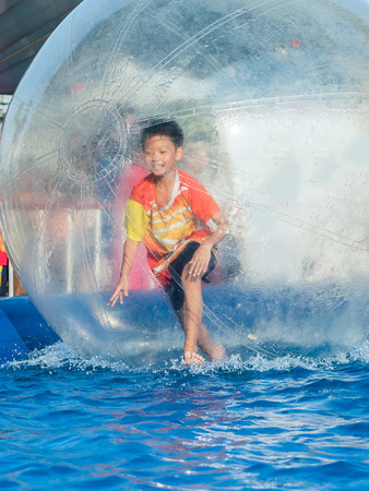 floating on water: Young Asian boy playing inside a floating water walking ball Stock Photo