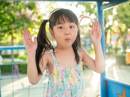 asian baby child playing on playground, in sunset light, peekaboo action Stock Photo