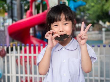 Happy Asian child eating delicious nori seaweed Stock fotó