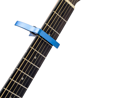Blue capo on guitar fingerboard, white background , close up