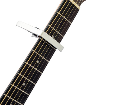 Silver capo on guitar fingerboard, white background , close up Stock Photo