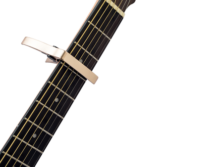 Gold capo on guitar fingerboard, white background , close up Stock Photo
