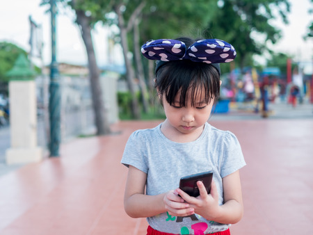 Asian child girl play smart phone, in the garden