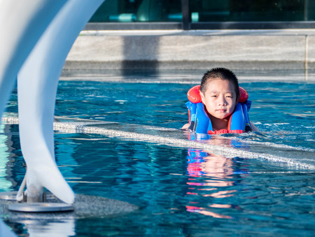 Asain boy in a swimming pool wearing a life vest, in sunset light Stock Photo