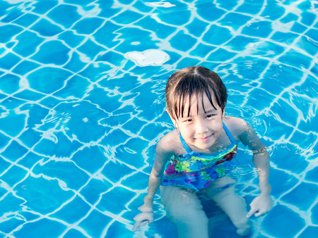 Asian girl is playing in the pool, sunset light