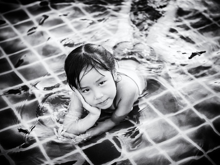 Asian girl is playing in the pool, laying down,  black and white Stock Photo
