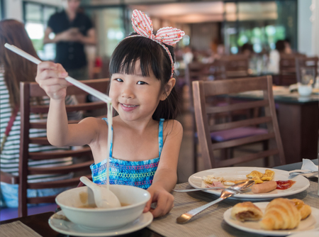 Happy Asian child eating delicious noodle with chopstick, in the restaurant
