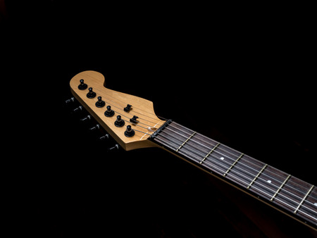 head of the electric guitar on black background
