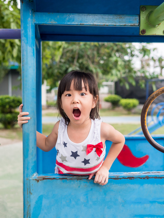 Happy asian baby child playing on playground, Girl gapes in surprise looking away Stock Photo