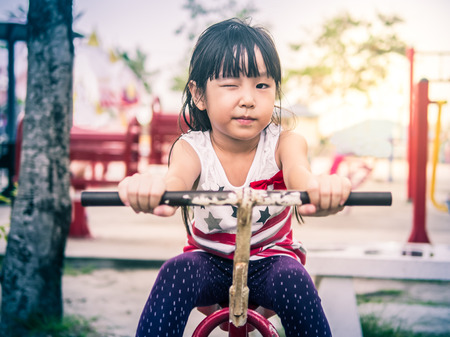 Happy asian baby child playing on playground, wink action,  sunset light in vintage style