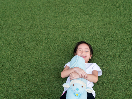 bolster: little asian kid girl lay down on the lawn with her doll