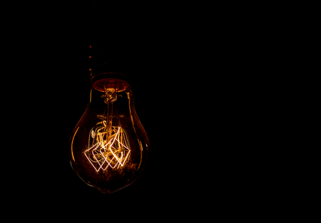 Vintage incandescent light bulb filament on black, close up shot