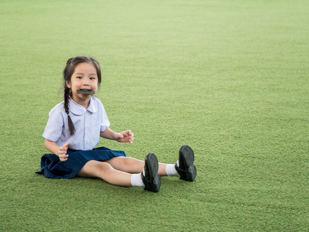 Happy Asian child eating delicious nori seaweed, in the garden Stock Photo
