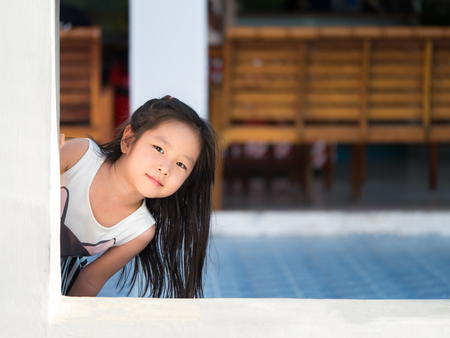 Adorable little girl playing peekaboo, asian child