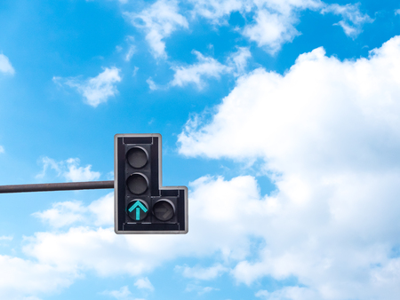 Green color on the traffic light with a beautiful blue sky in background, Go straight