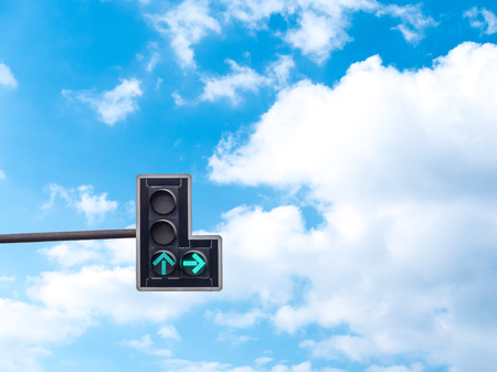 Green color on the traffic light with a beautiful blue sky in background, Go straight and turn right