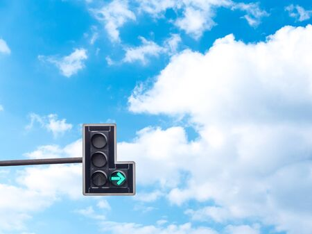 Green color on the traffic light with a beautiful blue sky in background, turn right
