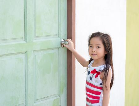 Little Asian girl kid try to open the door