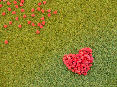 heart shape made from candle on artificial grass, selective focus