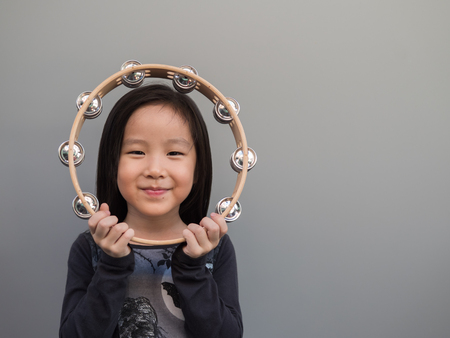 Little asian child play the tambourine, gray background Stok Fotoğraf