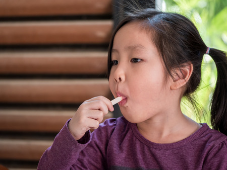 Little Asian girl eating ice cream, wood shade stripes background Stock Photo