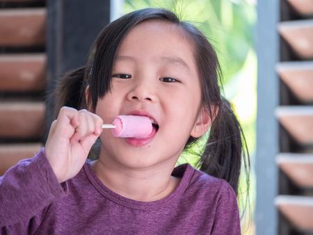 Little Asian girl eating ice cream, wood shade stripes background Stock Photo