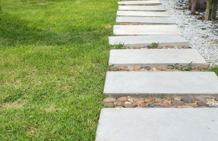 Landscaping in the green garden. pathway in park, with stone tile on green grass field Stock Photo