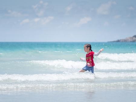 little Asian girl run play waves on the beach , run and jump action