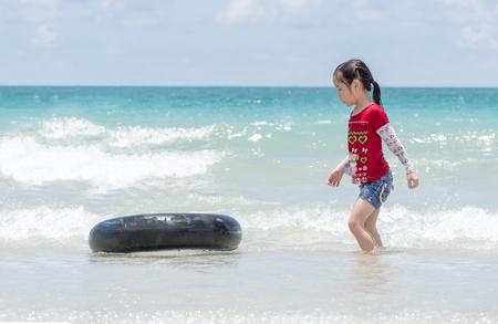 little Asian girl run play waves on the beach , with a ifebuoy