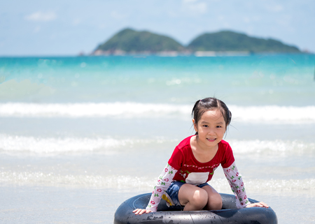little Asian girl run play waves on the beach , sit on a ifebuoy