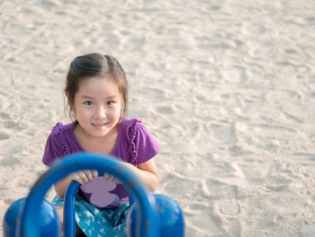 happy Asian child on a seesaw , sand background