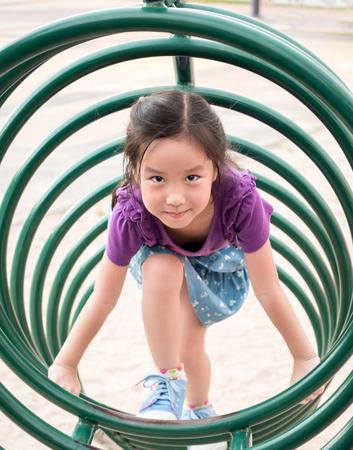 Happy kid, asian baby child playing on playground, climb the playground equipment, circle shape