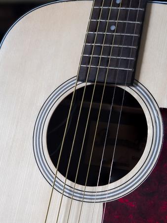 Close up shot of acoustic guitar. Strings, sound hole , bridge, pickguard