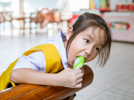 Little Asian girl eating ice cream, in summer Banco de Imagens