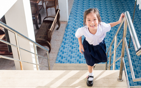 second floor: Little Asian  girl going up the stairs in the school, uniform
