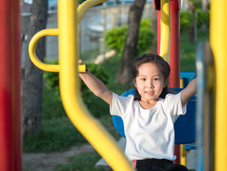 Happy asian baby child playing on playground , exercise equipment in the garden