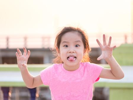 Junge niedlichen frechen Mädchen, Händchen haltend mit fünf Fingern tragen rosa T-Shirt, haften ihre Zunge für lustiges Gesicht