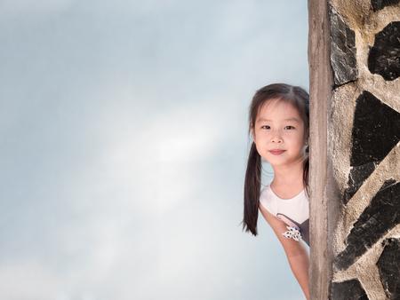 Asian girl hiding behind the wall, peekaboo action Stock Photo