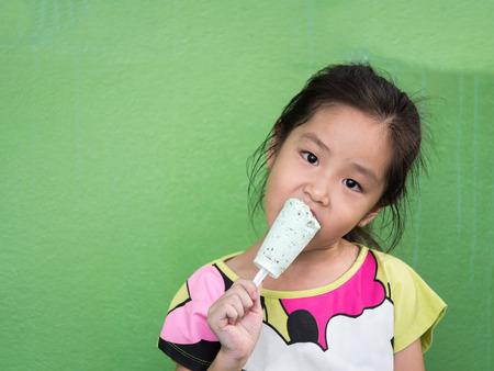 Little Asian girl eating ice cream, in summer Stock Photo