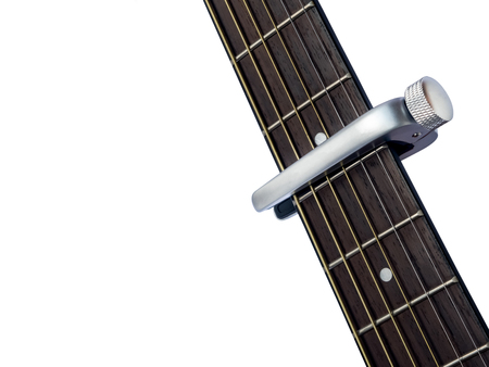 capo on guitar fingerboard, white background , close up Stock Photo