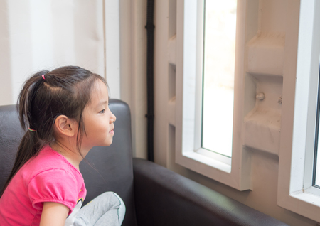 Beautiful little girl watching out the window. sit on the sofa Stock Photo