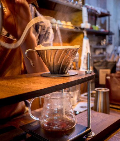 Hand drip coffee. Barista pouring water from silver teapot Stock Photo