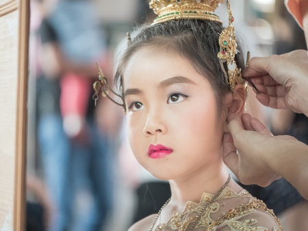 Mother help her daughter to dressed up her Thai traditional dress , National Costumes