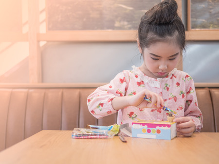 Asian little kid girl play the edible toy on the wood table Stock Photo
