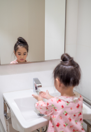 Asian little kid girl wash her hand in the toilet