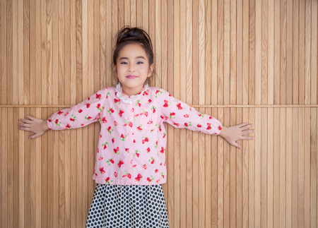 Portrait of happy little girl , showing two hands, wood background