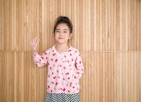 Portrait of happy little girl , wood background, show four fingers